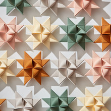 Pattern Of Multicolored Paper Origami Stars On A Gray Background With Shadows. Creative Christmas Background. Flat Lay