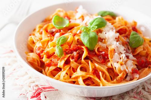 Fotografia  tagliatelle pasta with tomato sauce parmesan basil