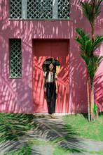 Beautiful Girl Posing Against The Pink Wall With Tree Shadows