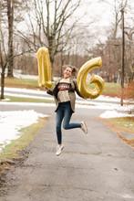 Teenage Girl Jumping Holding Sixteen (16) Balloons