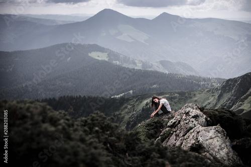 Pinturas sobre lienzo  Young woman sitting on a mountain top