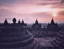Buddha Statue And Borobudur Temple At Colorful Sunrise