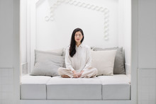 A Woman Meditating On A Bed