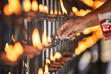 Hand Lighting Candle At Temple Of The Sacred Tooth Relic, Kandy, Sri Lanka
