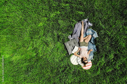 Top view of relaxed woman with book lying on a meadow - 288208402