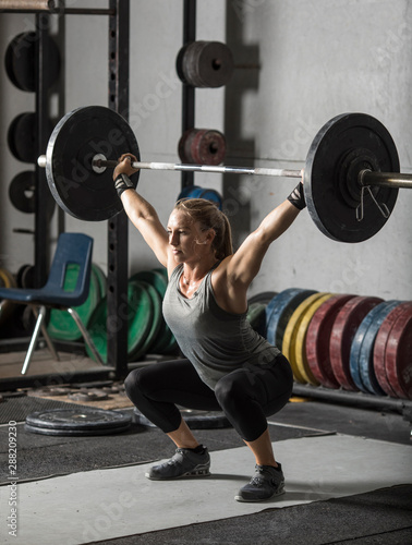 Fototapeta  Young, strong, female weight lifter practicing snatch in weight room with heavy barbell