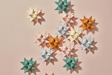 Handcraft Colorful Origami Stars On A Light Brown Background With Reflection Of Shadows And Copy Space. Flat Lay