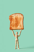 Miniature Articulation Mannequin Holds Fresh Toast In His Hand On A Green Background, Copy Space.
