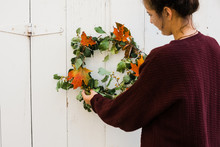 Young Woman Hanging A Fall Wreath On A Barn Door