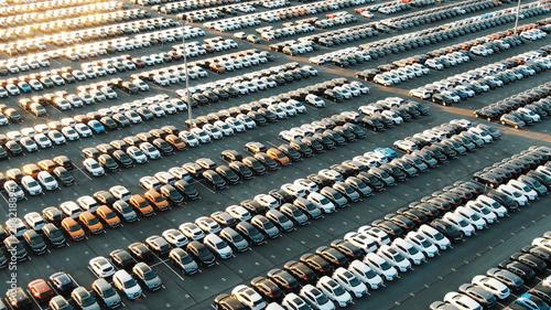 Obraz multicolored cars on warehouse parking lot lit by sunset - fototapety do salonu