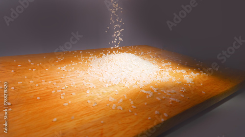 Vászonkép  Rice grits in a pile on a wooden board
