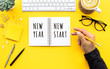 Leinwanddruck Bild - New year new start text with youngman writing on notepad on color desk table.Business goal-plan-action and resolution concepts