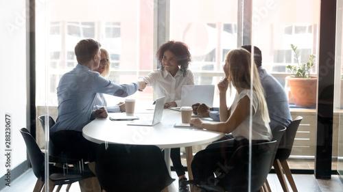 Montage in der Fensternische Akt Smiling diverse employees handshake greeting at office meeting