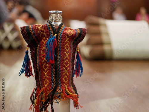 Fényképezés A bottle of water in a bottle holder - colorful hilltribe shirt style, with a de