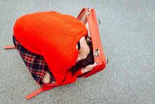 Overhead View Of Woman In Red Sweater Hiding In Open Suitcase