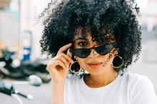 Pretty Ethnic Woman In White T-shirt And With Black Curly Hair Looking At Camera Over Black Glasses