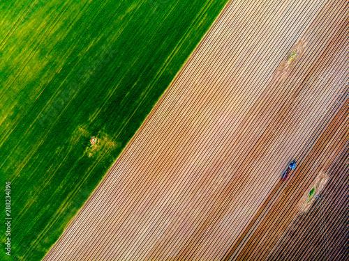 Obraz na plátně Farmer in tractor preparing land with seedbed cultivator in farmlands
