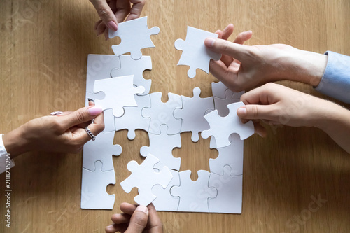 Obraz na plátne Top view of diverse people assemble jigsaw looking for solution