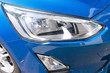 headlight detail of modern blue luxury car with projector lens for low high fog beam