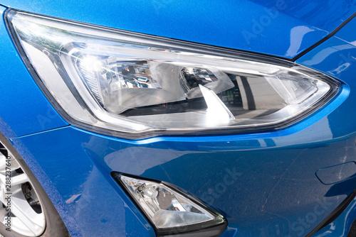 Fototapeta headlight detail of modern blue luxury car with projector lens for low high fog beam obraz na płótnie