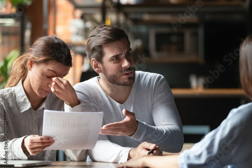 Stampa su Tela Angry young couple complaining, bad contract terms, arguing with manager