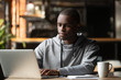 canvas print picture - African American man using laptop in cafe, looking at screen