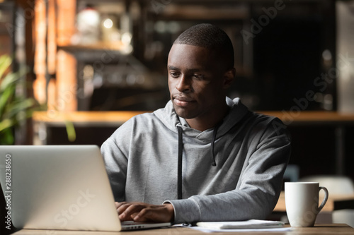 Photo Stands Coffee bar African American man using laptop in cafe, looking at screen