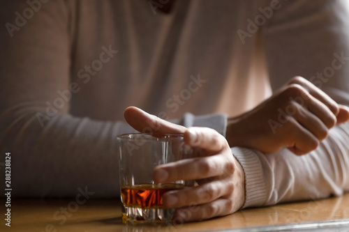 Foto auf Leinwand Alkohol Close up man holding glass with alcohol in hand, drinking alone