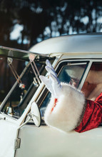 Cheerful Senior Man In Costume Of Santa Claus Sitting In Old Van And Waving Hand From Open Window Looking Away