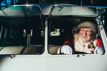 Smiling Senior Man In Costume Of Santa Claus Driving Old Van With Metal Bell In Hand On Sunny Day Looking Away