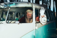 Cheerful Senior Man In Costume Of Santa Claus Sitting In Old Van And Waving Hand From Open Window