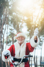 From Below Senior Man In Costume Of Santa Claus Sitting On Cycle, Ringing Bell And Looking At Camera