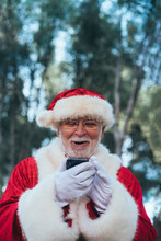 From Below Joyful Man In Costume Of Santa Claus Using Modern Mobile Phone On Blurred Nature Background