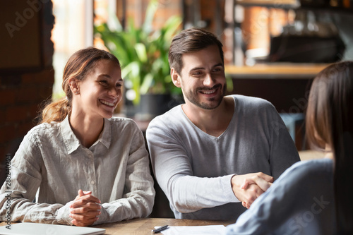 Smiling couple making deal, husband shaking hand of broker or realtor Canvas Print