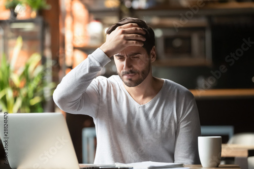 Upset man working in cafe, suffering from headache, touching forehead Billede på lærred