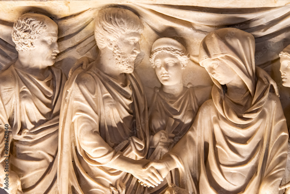 Fototapety, obrazy: Classical sculptures carved on marble showing ancient roman man and woman shaking hands while observed by goddess