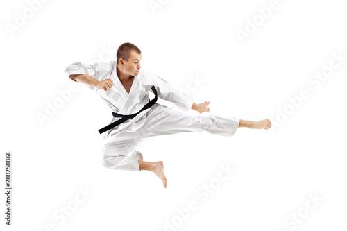 man exercising karate, kick in the air against white background Wallpaper Mural