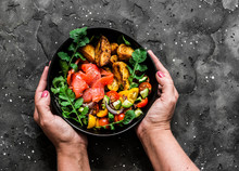 Smoked Salmon, Baked Potatoes, Fresh Vegetables Salad Breakfast Bowl In Women's Hands On A Dark Background, Top View