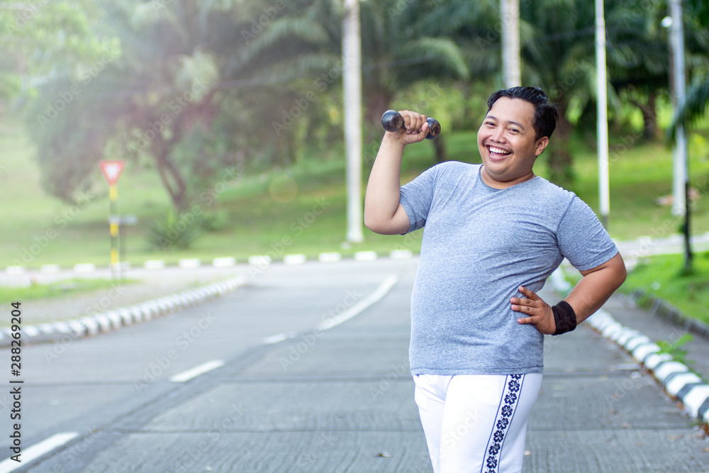 Fototapety, obrazy: Asian young man with obesity confidently lifts a barbell and poses in front of the camera