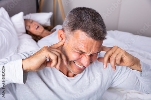 Photo An Angry Man With Snoring Wife On Bed