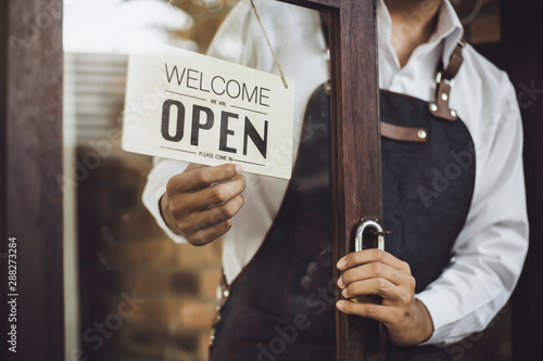 Store owner turning open sign broad through the door glass and ready to service.