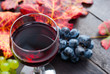 Leinwanddruck Bild - glass of red wine and grapes on black wooden table background