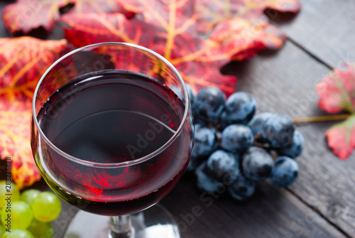 Acrylic Prints Wine glass of red wine and grapes on black wooden table background