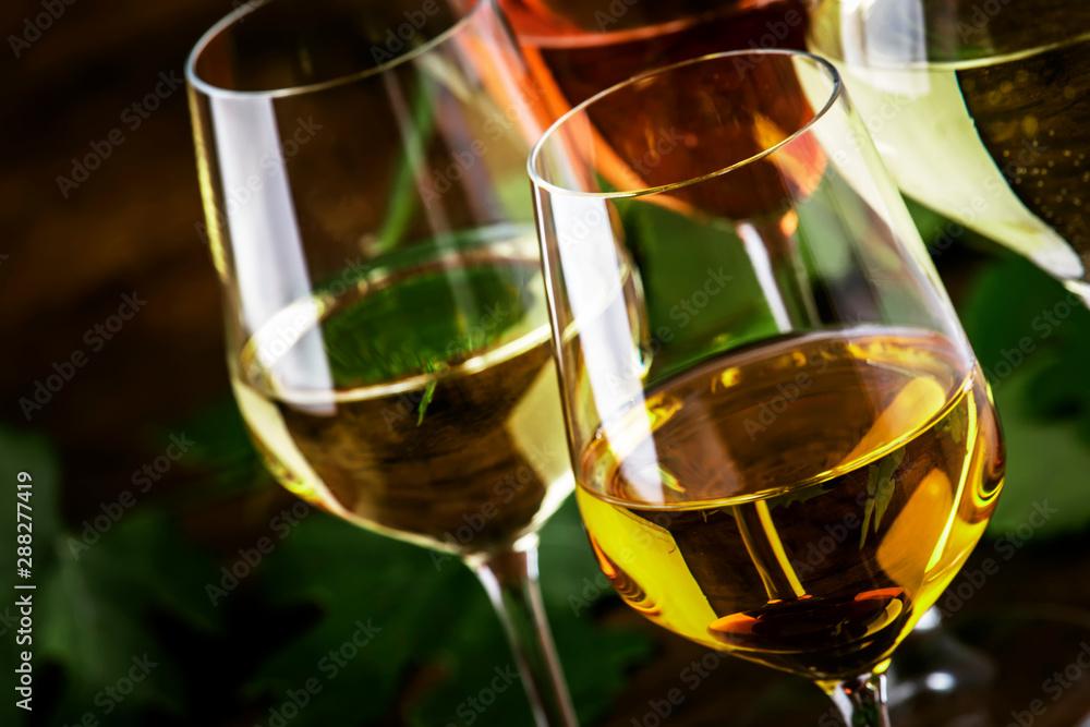 Fototapeta White wine set. Wine tasting, the most popular varieties of white wines in wine glasses on vintage wooden table in rustic style, selective focus