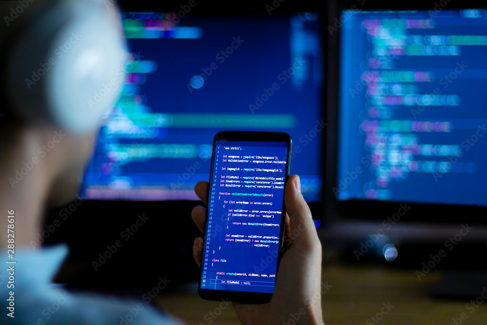 Fototapeta Software developer freelancer with white headphones and glasses working with program code: C++ Java, Javascript on wide displays and smartphone at night. Develops new web, desktop, mobile application.