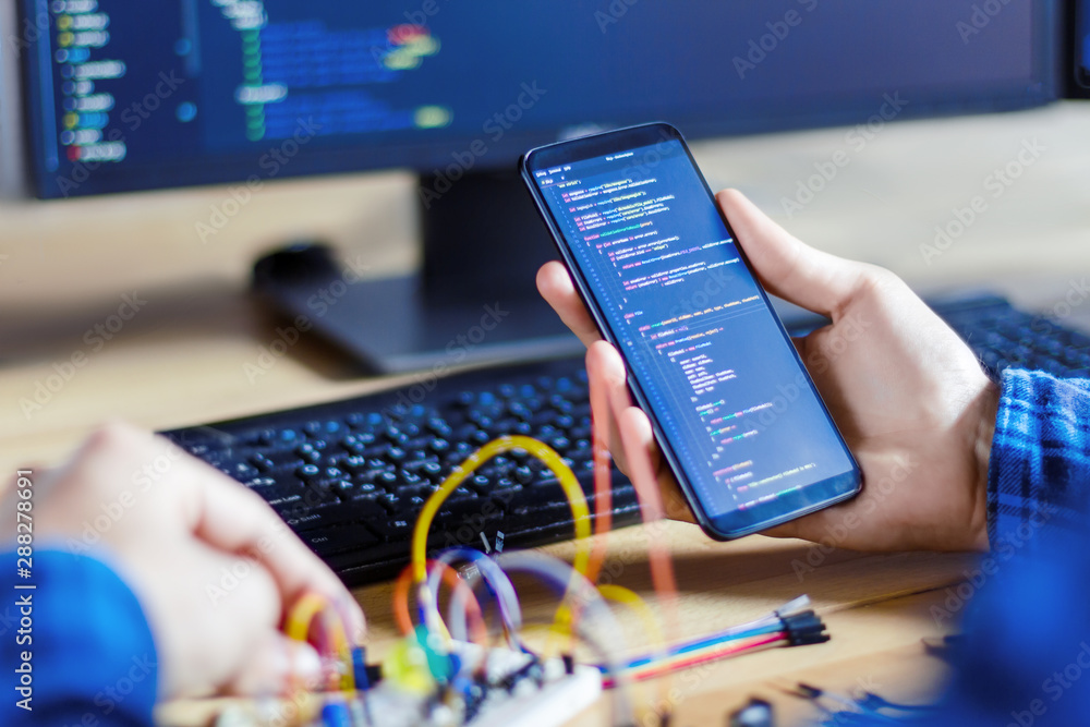 Fototapety, obrazy: Developer is connecting breadboard to microcontroller. Man is holding smartphone with program code software for controlling electronic device. Chips, resistors, diodes on desktop of hardware engineer.
