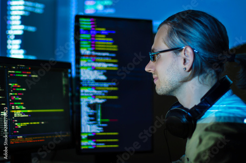 Fototapety, obrazy: Software developer freelancer man male in headphones work with program code C++ Java Javascript on wide displays at night Develops new web desktop mobile application or framework. Projector background