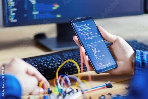 Obraz Developer is connecting breadboard to microcontroller. Man is holding smartphone with program code software for controlling electronic device. Chips, resistors, diodes on desktop of hardware engineer. - fototapety do salonu