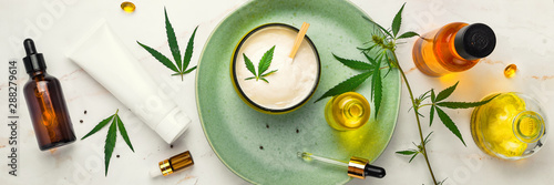 Valokuvatapetti Bank of medicinal cream with CBD oil, bottle of cannabis oil, capsules, on a green plate