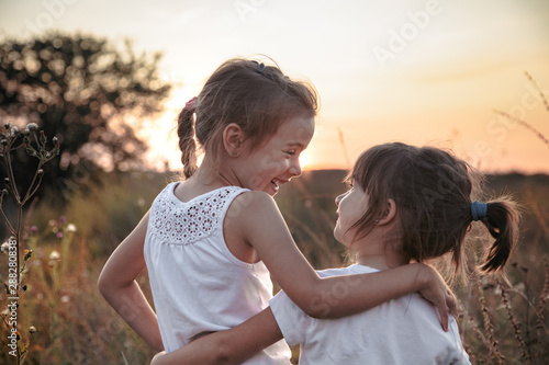 Two little sisters in a field at sunset. Canvas Print